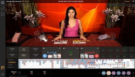 Baccarat dealer standing in front of a table.