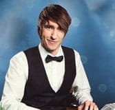 A male dealer from Evolution Gaming is sharply dressed in a waistcoat and bowtie.