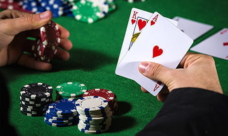 a king of clubs and an ace of clubs in a players hand with casino chips on a green felt table.