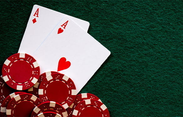 Two Aces of Hearts and red casino chips on a green felt background.