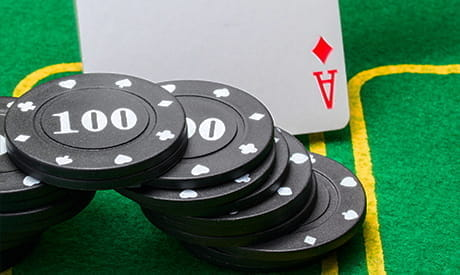 one card faceup on a playing table with a stack of casino chips next to it.