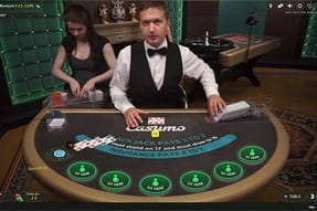A female live dealer in a red dress at the Casumo blackjack table.