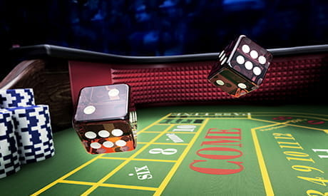two dice in the air above a craps table in a land-based casino.