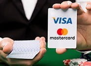 An image showing a casino player holding a stack of cards showing the logos of credit card companies.