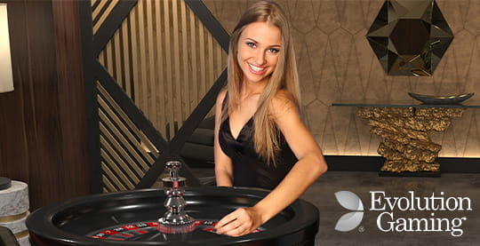 A croupier from the Evolution Gaming Live staff sitting behind a roulette table.