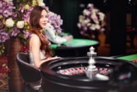 Small image of a female dealer, wearing an elegant dress, at a roulette wheel, surrounded by lavish decoration, from the Evolution Gaming live studios.