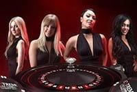 Four female dealers, all dressed in black, from Extreme Live Gaming stand behind a roulette wheel with dark red lighting in the background.