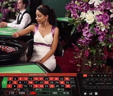 A Karamba live casino dealer at a roulette table.