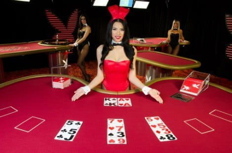 A female dealer wearing a red Playboy Bunny outfit deals a hand of blackjack in the old Microgaming live studios.