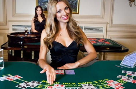 A female live dealer wearing a classy black dress sits behind a live blackjack table, holding her hand out to invite you to join her.