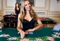 Small image of a female dealer seated at a blackjack table, ushering new players to the table with her hand, from the Playtech live studios.