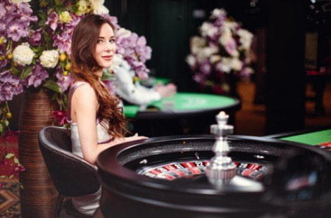 A live female casino games dealer sits in a glamorous room behind a roulette wheel.