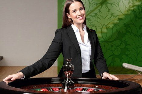 A smiling female croupier in a classic suit holds a roulette wheel, ready to play the game.