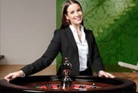 Small image of a female dealer, dressed in a suit and white shirt, standing behind a roulette wheel, smiling at the camera while in the NetEnt live studios.