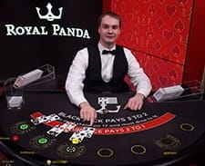 An image of a live dealer setting up a blackjack game.
