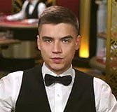 In a crowded live casino games studio, Thomas waits to deal a game while wearing eveningwear.