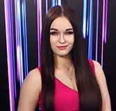 Long dark hair and a bright pink dress suit Playtech live game dealer, Ilana.