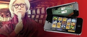 A man with a mustache and a mobile device in a casino.
