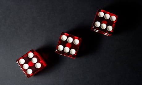 Three red dice on a black table.
