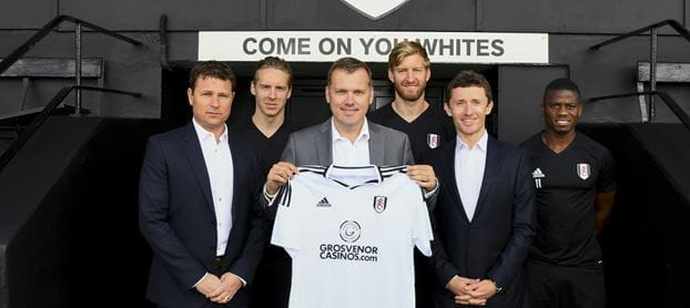 Fulham FC representatives hold up a home shirt with the new Grosvenor logo