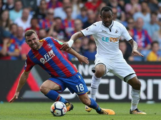 Crystal Palace and Swansea players compete in a Premier League Match