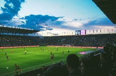 A stock image of fans enjoying a football game in a stadium