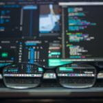 Glasses resting in front of a computer screen with lots of code and data.