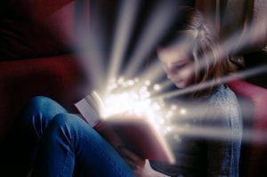 A young girl reading a book emitting sparks.