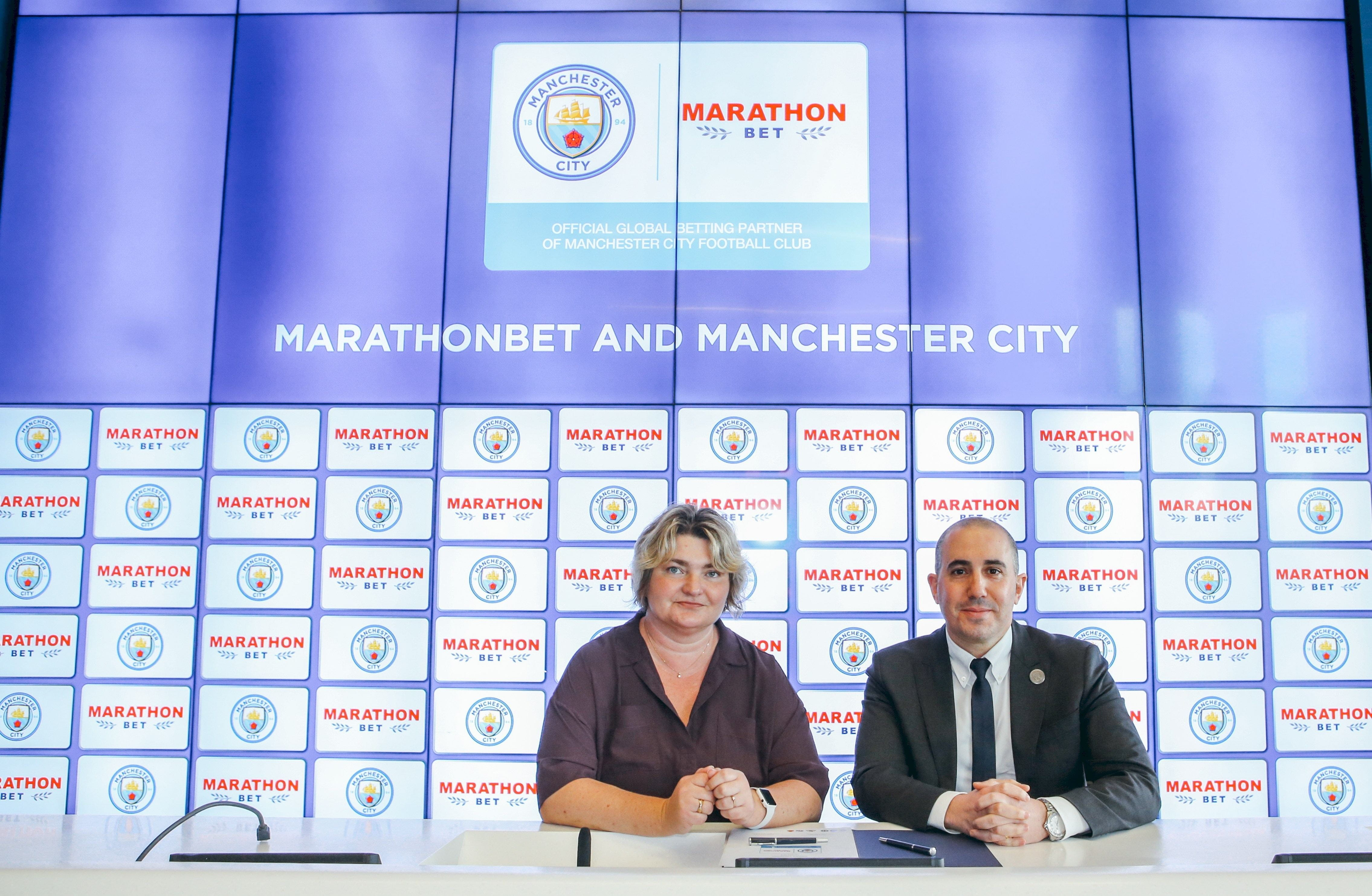 Damian Willoughby and , Natalia Zavodnik signing an agreement between Marathonbet and Manchester CIty.
