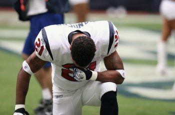American football player drops to his knees during a game.