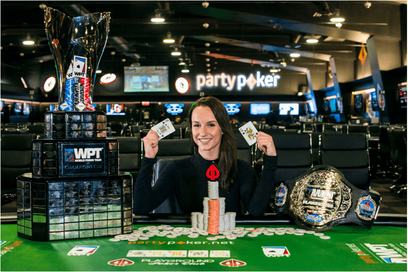 Ema Zajmovic sitting behind a poker table. On the table is her victory belt and playing cards.