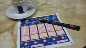 A EuroMillions lottery slip, pen and a cup of coffee.