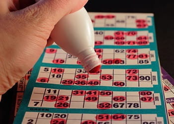 A bingo stamper stamping numbers on a card,
