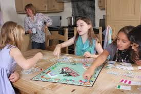 A picture of three young girls playing Monopoly.