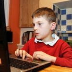 Young boy in school uniform sat at a computer.