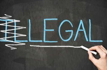 "The word ""illegal"" written on a chalkboard, with the first two letters scored out, so that it reads ""legal""."