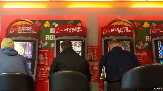 Three players sitting at fixed-odds betting terminals.
