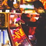 A person playing a slots machine in a brightly lit casino