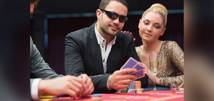A casino player with playing cards, and a woman looking at his cards.