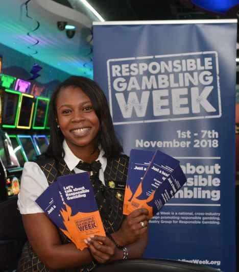 Woman holds leaflets in front of banner at Responsible Gambling Week event.
