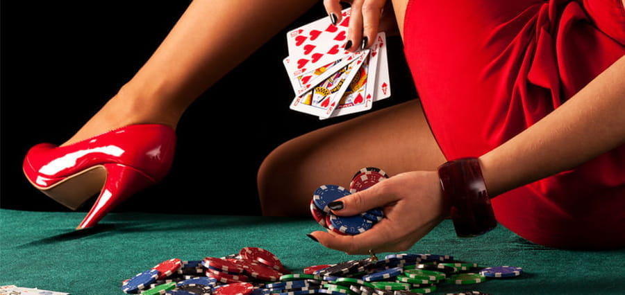 A woman holding casino chips and cards, while placing her high-heeled foot on a casino table.