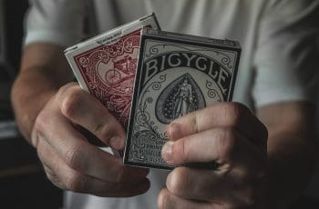 Two packs of playing cards being held up.
