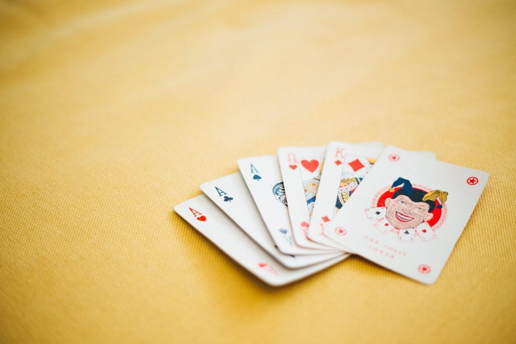 Playing cards on a table, with three Aces, a Queen, a King and a Joker showing.