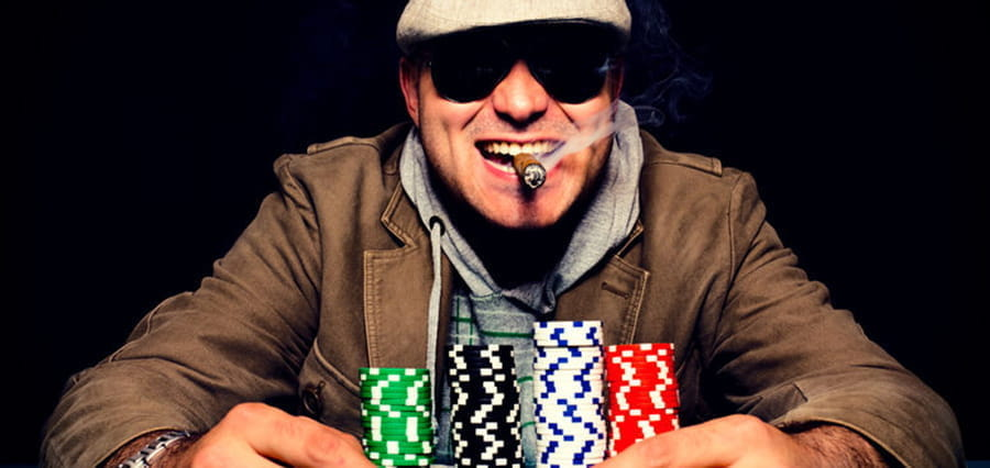 A gambler smoking a cigar, holding stacks of casino chips.