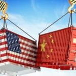 Two shipping containers, with the American and Chinese flags, crashing into each other.