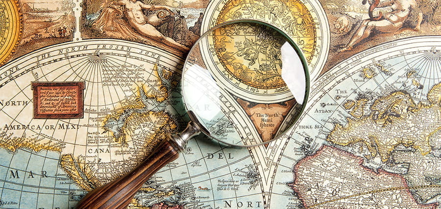 Ancient world maps and a magnifying glass.