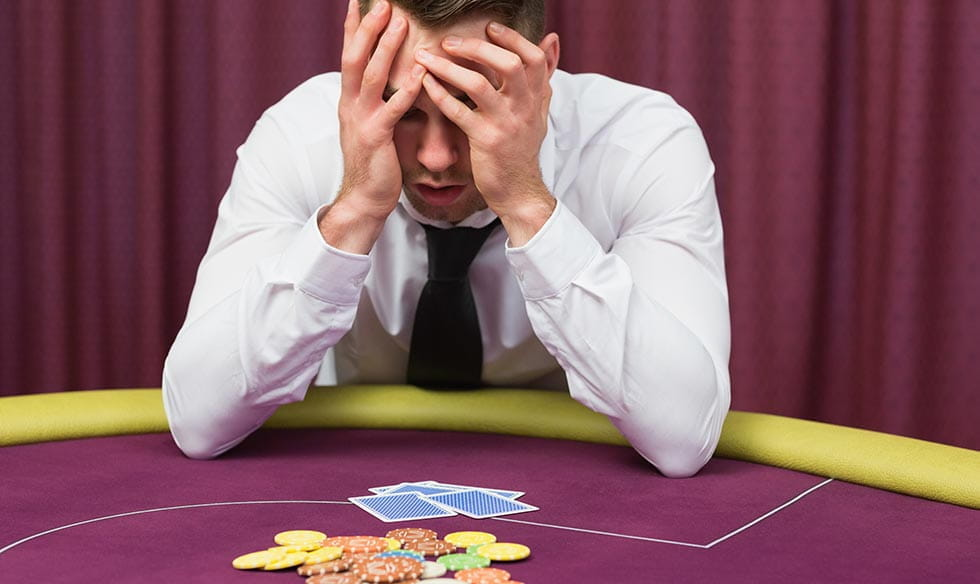 A poker player with their head in their hands.