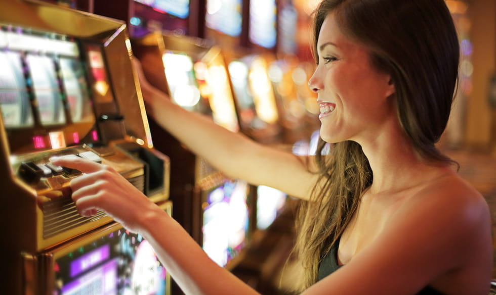 A woman playing on a slot machine.