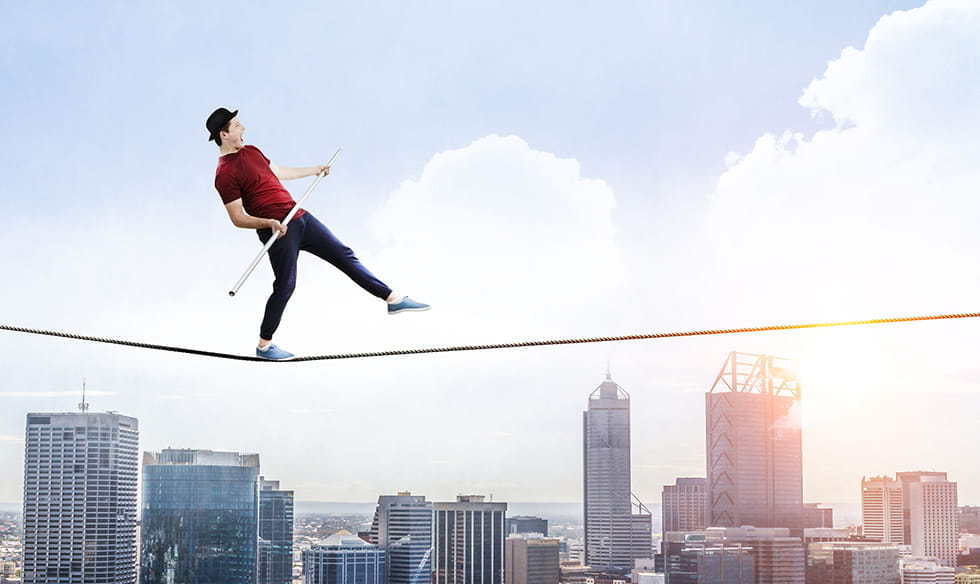 A man walking across a tightrope, over a cityscape.