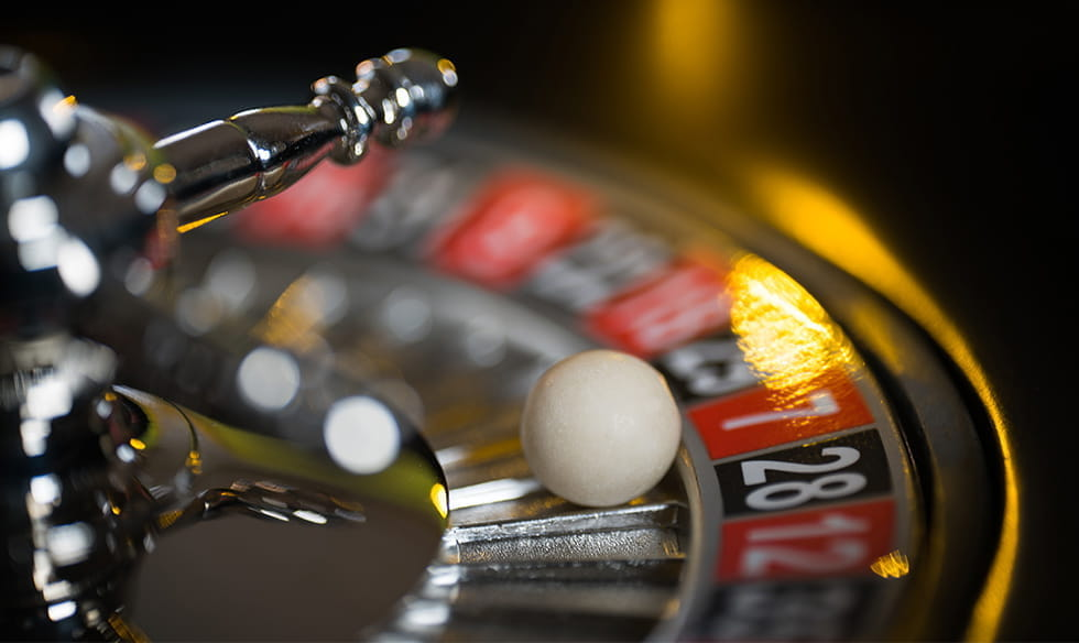 A ball sitting in a roulette wheel pocket.